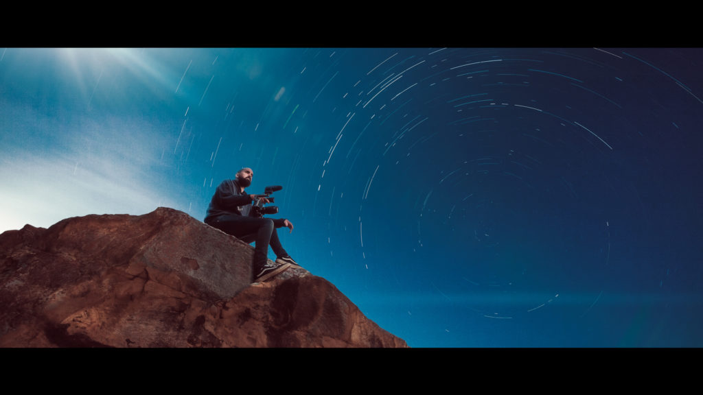 the image engineer sitting on a rock underneath a starry sky